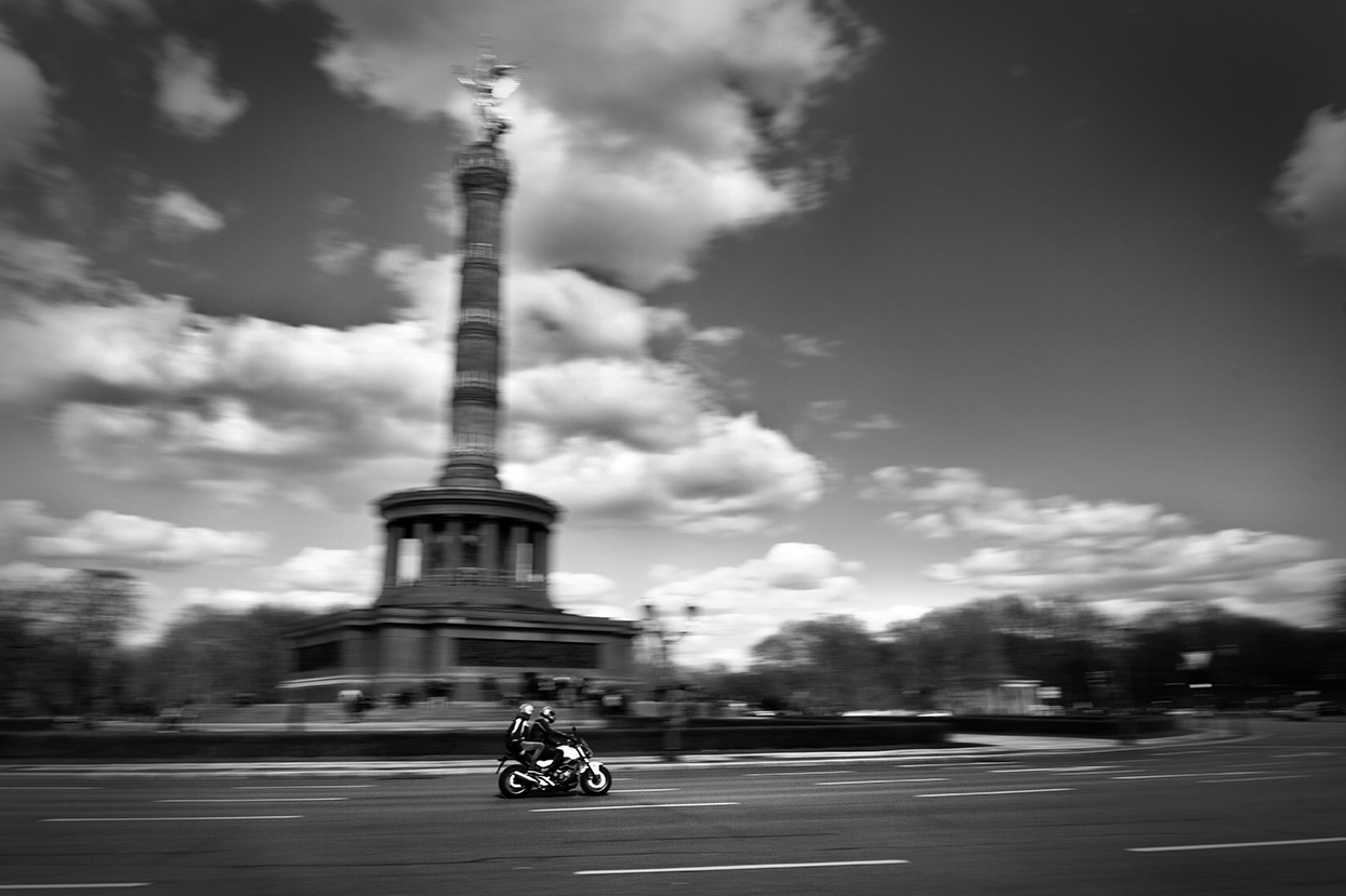 Great ride: a couple rides a motorbike in the area of Siegessäule (Berlin, Germany).